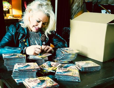 Kim signing 'Here Come The Aliens' CD's
